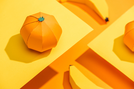 Selective Focus of paper tangerine on cardboard with origami bananas on orange background