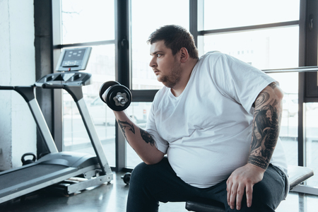 Overweight tattooed man exercising with dumbbell at sports center
