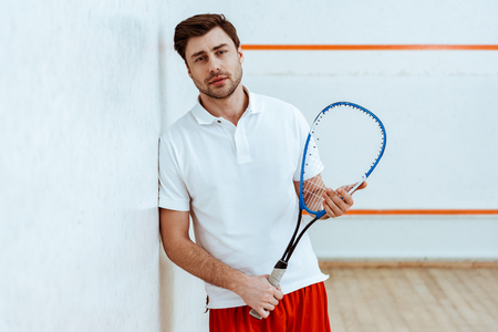 Bearded squash player holding racket and looking at camera