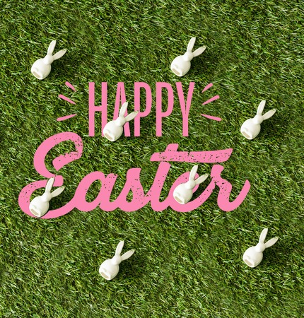 top view of decorative bunnies on green grass with pink happy Easter lettering