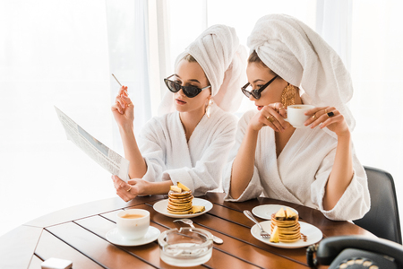 stylish women in bathrobes, sunglasses and jewelry with towels on heads smoking cigarette and reading newspaper while having breakfast