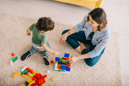 High angle view of mom and son playing with toy blocks in living room