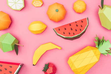Top view of handmade colorful origami fruits on pink background