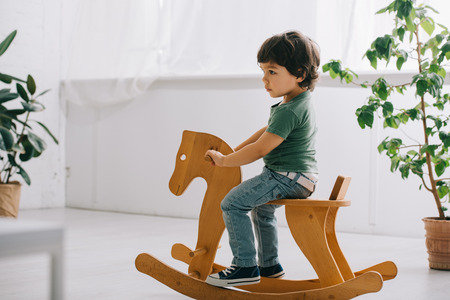 child sitting on wooden rocking horse in living room Stock Photo