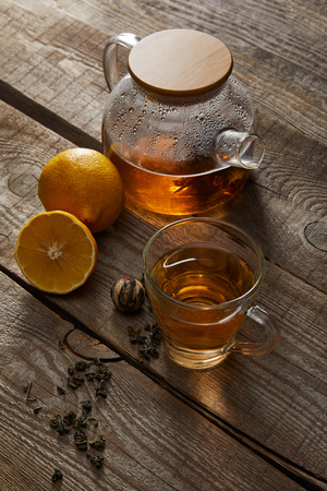 Transparent teapot with cup of traditional Chinese blooming tea and lemons on wooden surface