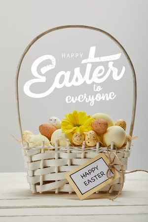 wicker basket with colorful painted eggs, yellow gerbera flower, greeting card and happy Easter to everyone lettering on grey background