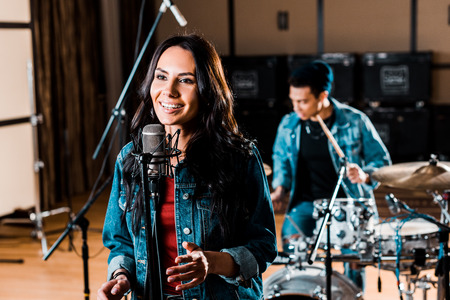 Pretty woman singing while mixed race musician playing drums in recording studio
