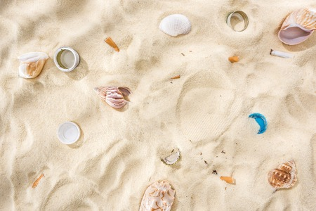 top view of seashells, bottle caps, scattered cigarette butts, plastic bottle caps on sand Stock Photo