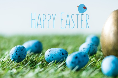 Blue painted quail eggs on green grass near golden chicken egg and happy Easter lettering
