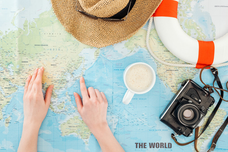 Cropped view of woman with cup of cappuccino, film camera, sunglasses, lifebuoy and straw hat pointing with finger on world map