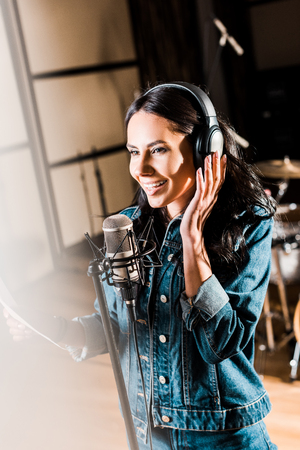 Selective focus of inspired woman in headphones singing in recording studio 写真素材