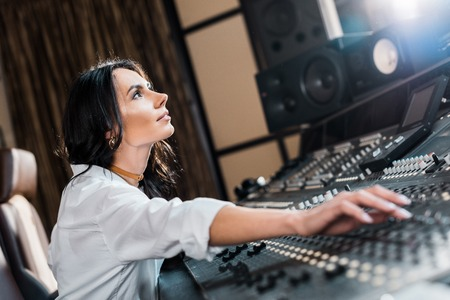 pretty smiling musician working in recording studio at mixing console in recording studio Imagens
