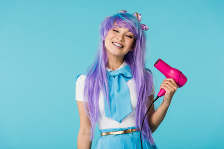 Smiling anime girl in wig using hairdryer with closed eyes isolated on blue background Stock Photo