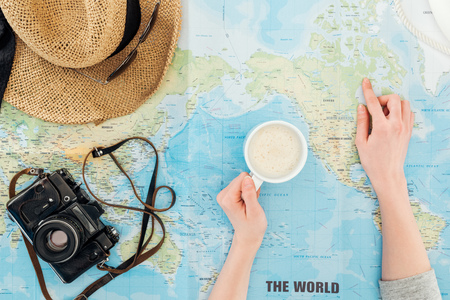 Cropped view of woman with cup of cappuccino, film camera, sunglasses and straw hat on world map Banque d'images - 121432521