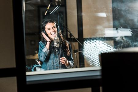 Beautiful, inspired musician singing near microphone in recording studio 写真素材