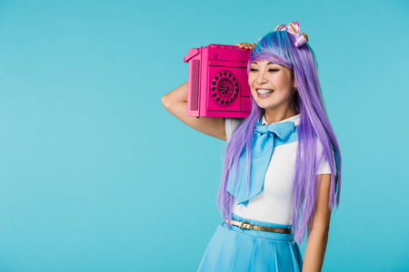 Smiling Asian otaku girl in purple wig holding boombox isolated on blue background