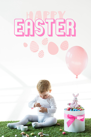 Cute baby sitting near box with colorful quail eggs, toy rabbit and air balloon on white background with happy Easter lettering Imagens