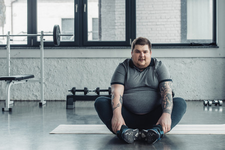 Overweight tattooed man sitting and looking at camera during stretching exercise at gym