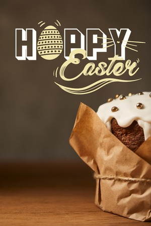 Close up of traditional Easter cake with sprinkles in craft paper with happy Easter lettering