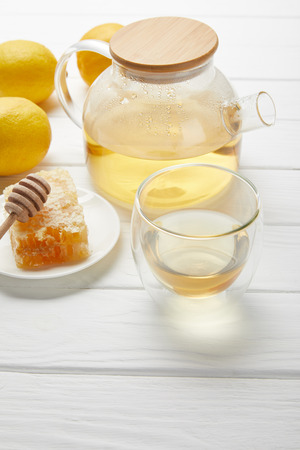 Teapot with organic herbal tea, glass, lemons and honeycomb on white wooden table