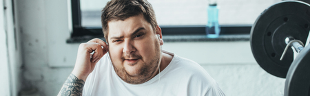 Panoramic shot of overweight man looking at camera while putting on earphones at gym