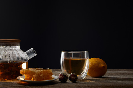 Transparent teapot with blooming tea, glass, lemon and honeycomb on wooden table isolated on black background Reklamní fotografie