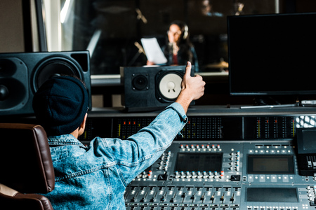 selective focus of mixed race sound producer showing thumb up to woman singing in recording studio Foto de archivo - 121432634