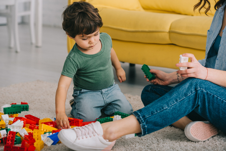 Cropped view of mother and son playing with toy blocks on carpet in living room