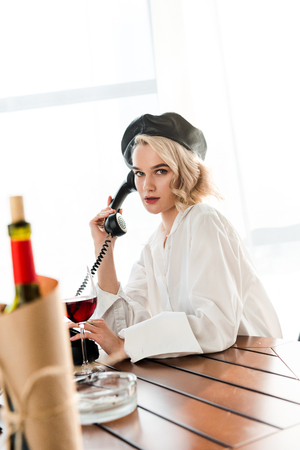 Selective focus of elegant blonde woman in black beret and white shirt sitting at table and talking o retro phone