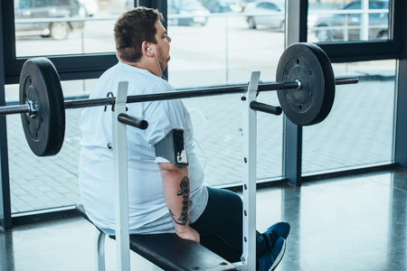 Overweight man in earphones sitting on bench and listening music at gym