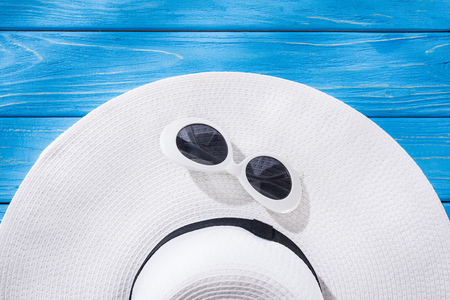 top view of white sunglasses and white floppy hat with black ribbon on blue wooden background Stock Photo