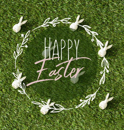 top view of decorative bunnies scattered on green grass with happy Easter lettering in circle