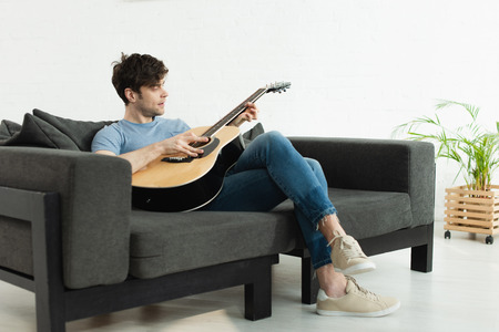 Handsome man sitting on sofa and playing acoustic guitar at home