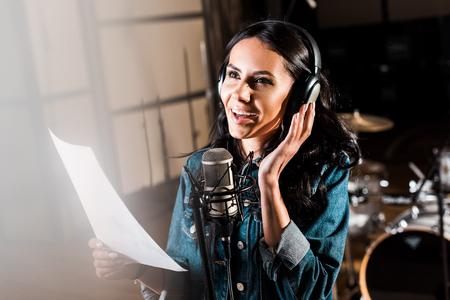 Selective focus of beautiful smiling woman in headphones singing in recording studio