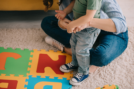 partial view of mother and son with alphabet puzzle mat on carpet Stock Photo