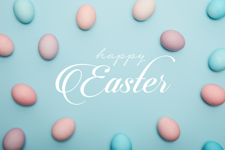 Top view of painted eggs on blue background with happy Easter lettering