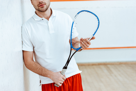 Partial view of bearded squash player holding racket in four-walled court