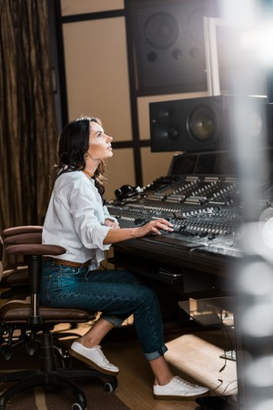 Selective focus of attractive sound producer working at mixing console in recording studio