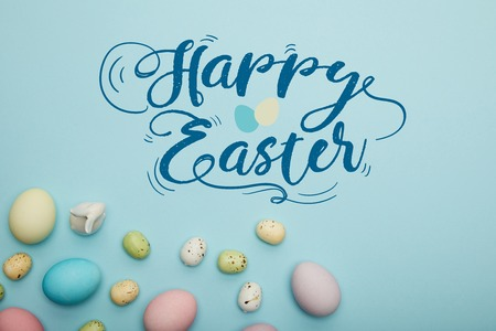 Top view of painted multicolored eggs scattered near decorative rabbit on blue background with happy Easter lettering