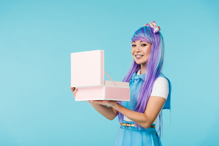 Smiling Asian anime girl holding open briefcase isolated on blue background
