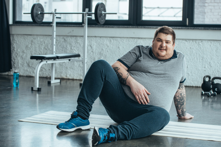 Overweight tattooed man looking at camera and sitting on fitness mat at sports center