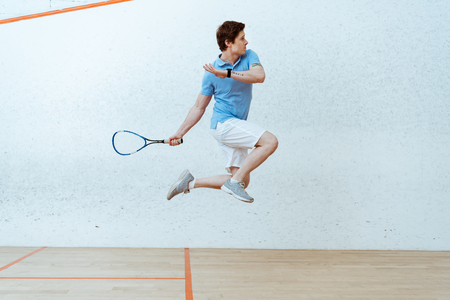 Sportsman in polo shirt jumping while playing squash in four-walled court