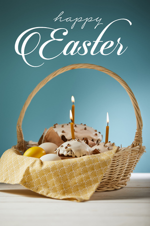 Traditional Easter cakes with burning candles and chicken eggs in wicker basket on blue background with happy Easter lettering