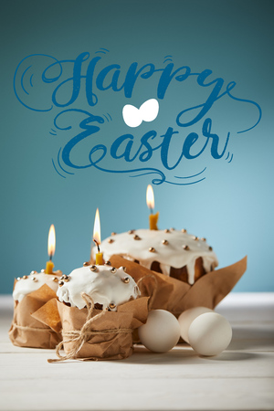 Traditional Easter cakes with burning candles and white chicken eggs on blue background with happy Easter lettering Banque d'images - 121432851
