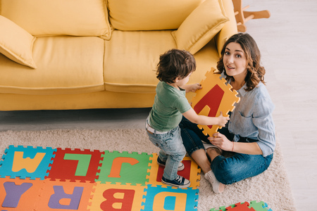 Smiling mother and kid playing with alphabet puzzle mat