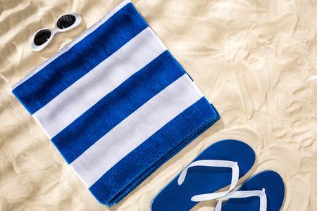 Draufsicht auf weiß-blau gestreiftes gefaltetes Handtuch, Retro-Sonnenbrille und Flip-Flops auf Sand