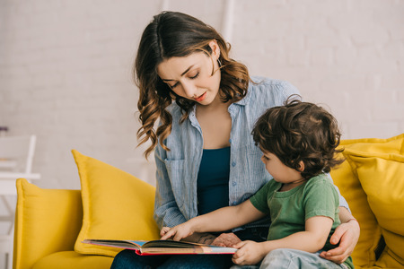 Mom and son sitting on yellow sofa and reading book Stockfoto