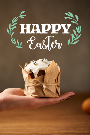 Cropped view of woman holding traditional Easter cake in craft paper with happy Easter lettering above