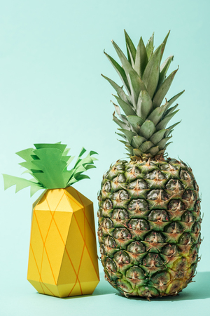 Handmade paper pineapple with fresh whole pineapple on turquoise background