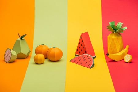Various handmade origami fruits on stripes of colorful paper background